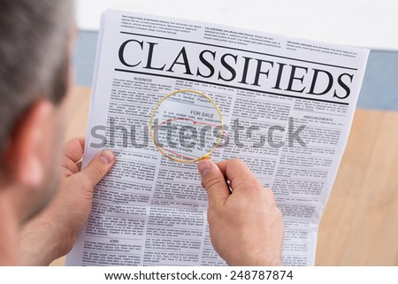 Close-up Of A Man Looking Classifieds Through Magnifying Glass - stock photo
