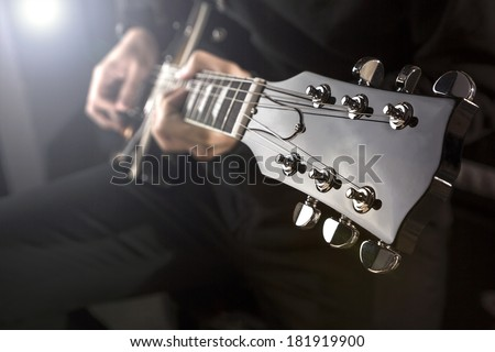 Close up of a man playing a guitar with spot light behind. - stock photo