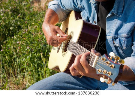 close up of a man playing an acoustic guitar in a sunny field - stock photo