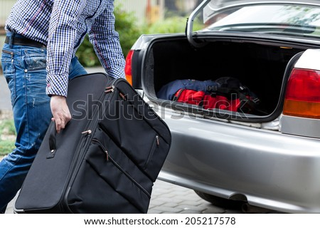 Close-up of a man putting suitcases in car trunk for a journey - stock photo