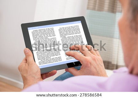Close-up Of A Man Reading Ebook On Digital Tablet - stock photo