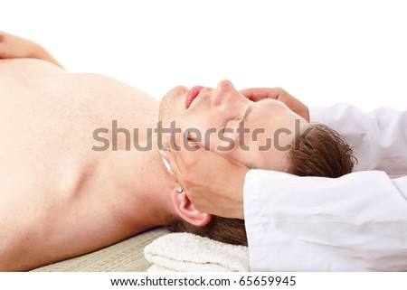 Close up of a man receiving facial massage from a woman - stock photo
