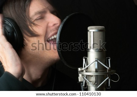 Close-up of a man recording vocals in a sound studio. - stock photo