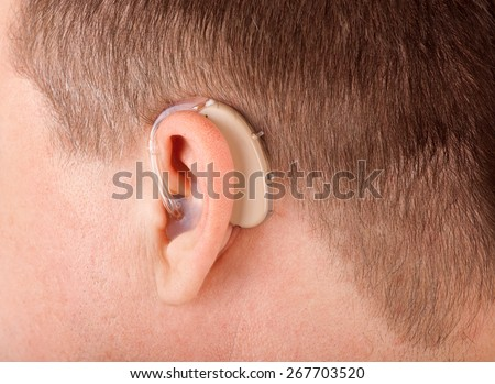 Close up of a man's ear with hearing aid - stock photo