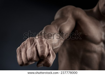 Close-up of a man's fist. Strong and power man's hand with muscles and veins. Studio shooting. - stock photo