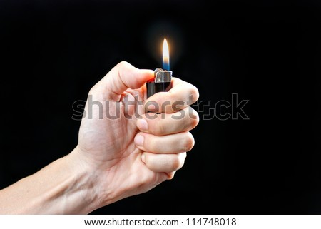 Close-up of a man's hand holding a lit lighter. - stock photo