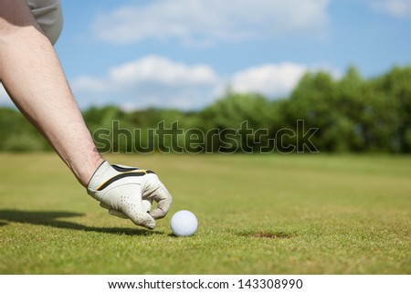 Close-up of a man's hand putting golf ball in hole at course - stock photo