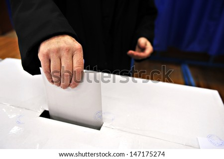 Close-up of a man's hand putting his vote in the ballot box - stock photo
