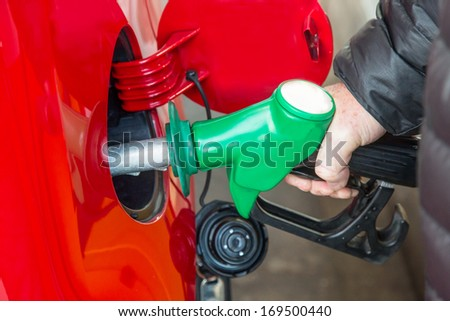 Close-up of a man's hand refilling a car with a petrol/gasoline pump - stock photo