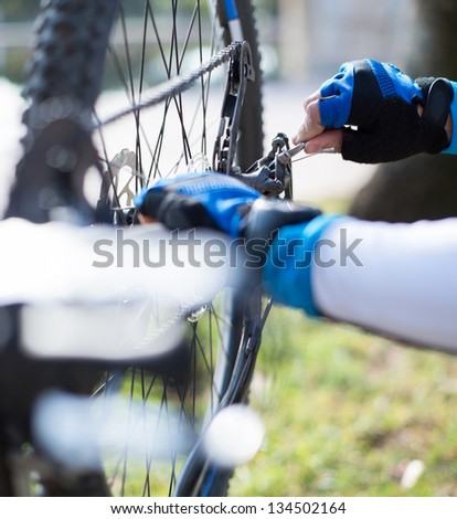 Close-up Of A Man's Hand Repairing Bicycle Wheel; Outdoors - stock photo