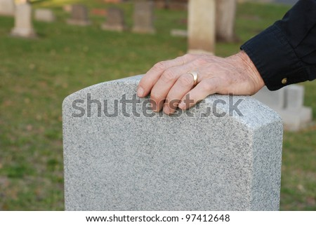 Close up of a man's hand, with wedding ring, resting on a headstone in a cemetery. - stock photo