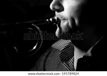 Close up of a man's lips and cheeks while playing a trumpet - stock photo
