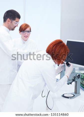 close-up of a man scientist supervising two women in a chemistry lab around lab tools analyzing chemical procedures - stock photo