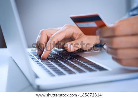 Close Up Of A Man Shopping Online Using Laptop With Credit Card - stock photo