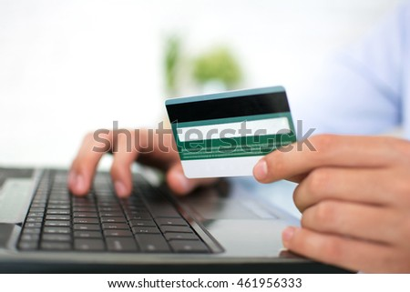 Close up of a man shopping online using laptop with credit card.