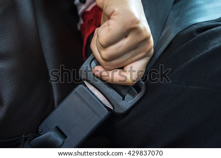 Close-up Of A Man Sitting In Car Fastening Seat Belt, Driver in business suit fastens his seat himself automobile seat belt, Woman sit on car seat and fasten safety belt, hands button safety belt. - stock photo