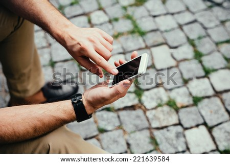 Close-up of a man sitting in the street and texting on his mobile - stock photo