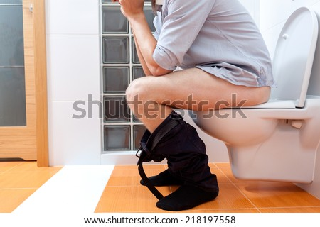 Close-up of a man sitting on a toilet