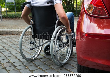 Close-up Of A Man Sitting On A Wheelchair Near His Car - stock photo