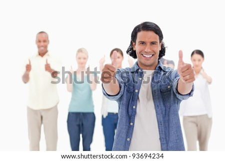 Close-up of a man smiling with his thumbs-up with people behind against white background - stock photo