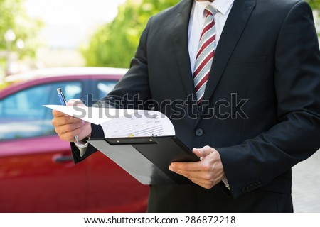 Close-up Of A Man Standing In Front Of Car Holding Clipboard In His Hand - stock photo