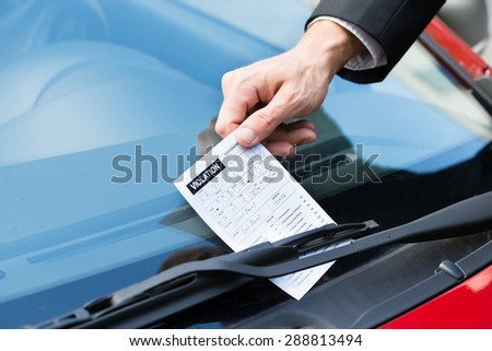 Close-up Of A Man Taking Parking Ticket On Car's Windshield