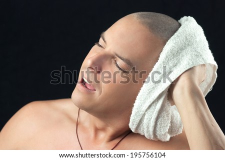 Close-up of a man towel drying his newly shaved head. - stock photo