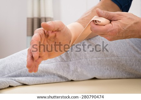 Close-up Of A Man Tying Elastic Bandage To His Wrist - stock photo