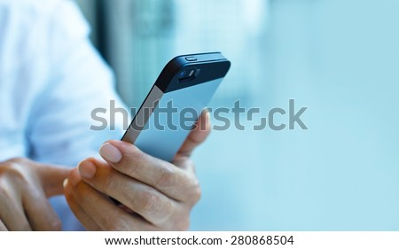 Close up of a man using mobile smart phone on pastel color tone, soft focus - stock photo