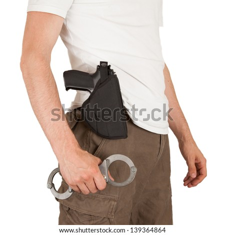 Close-up of a man with a gun and handcuffs, isolated on white - stock photo