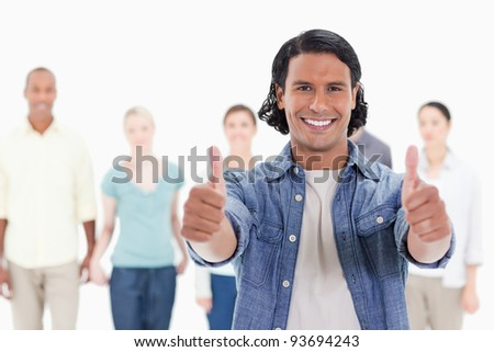 Close-up of a man with his thumbs-up with people behind against white background - stock photo