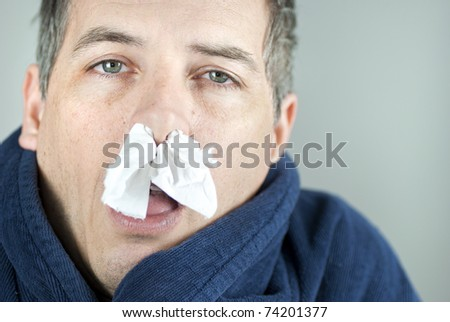 Close-up of a man with tissue in his nose. - stock photo