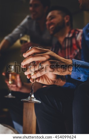 Close up of a mans hands holding a glass of wine in a bar. There are two men laughing in the background. - stock photo