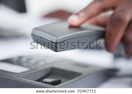 Close up of a masculine hand holding a phone handset against a white background - stock photo