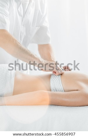 Close up of a masseur doing back massage at spa studio, light interior
