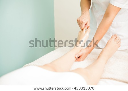 Close up of a masseuse giving a foot massage to a client at a spa. Plenty of copy space