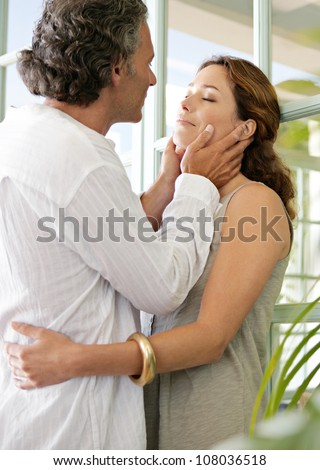 Close up of a mature couple hugging in a home terrace with large french doors. - stock photo
