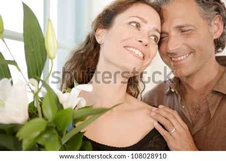 Close up of a mature couple with bunch of flowers at home. - stock photo