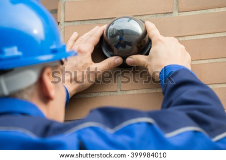 Close-up Of A Mature Male Technician Installing Camera In Building - stock photo