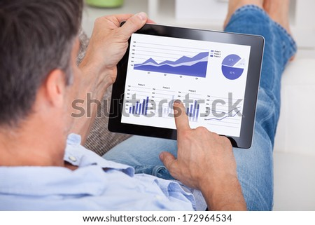 Close-up Of A Mature Man Analyzing Graph On Digital Tablet - stock photo