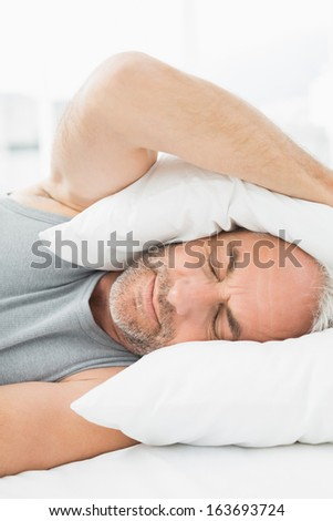 Close-up of a mature sleepy man covering ears with pillow in bed at home