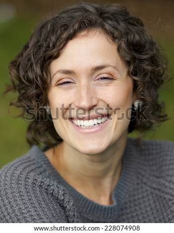 Close-up Of A Mature Woman Smiling At The Camera. She is serene and in peace. - stock photo