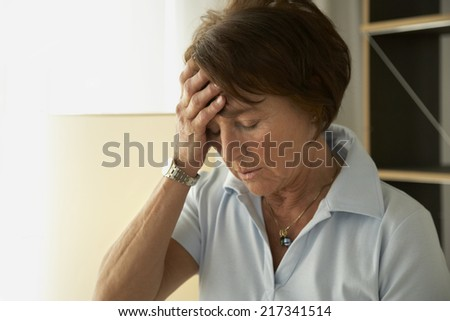 Close-up of a mature woman with a headache - stock photo