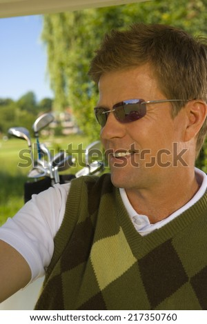 Close-up of a mid adult man in a golf cart and smiling - stock photo