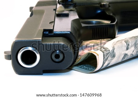 Close up of a 9mm gun and dollars - stock photo