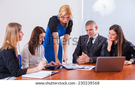Close-up of a modern business team using tablet computer to work with financial data in office