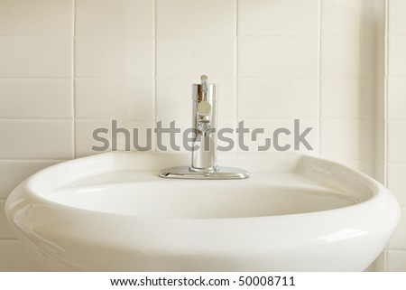 Close Up Of A Modern Stainless Steel Faucet On An Oval, White Porcelain  Pedestal