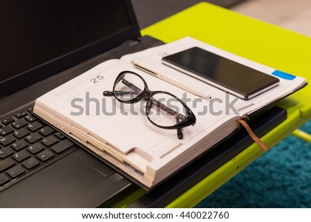 Close up of a modern tabletop workstation with stylish eyeglasses, a diary and mobile phone lying on the keyboard of laptop - stock photo