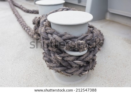 Close-up of a mooring rope with a knotted end tied around a cleat on a wooden pier/ Nautical mooring rope - stock photo