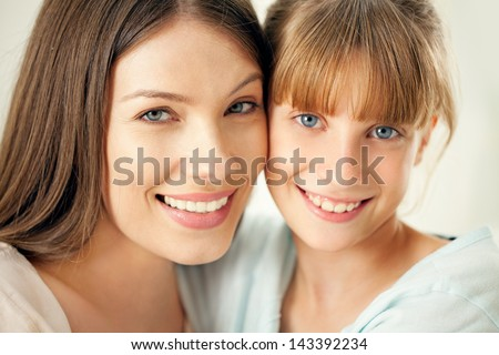 Close-up of a mother and her cute daughter smiling and posing. - stock photo